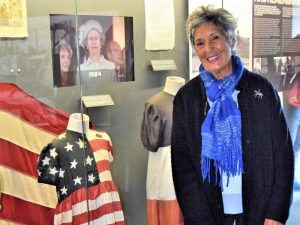 Danièle Patrix standing in front of the iconic American flag dress that she wore as a little girl
