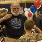 An older veteran saluting a young boy who is saluting him back
