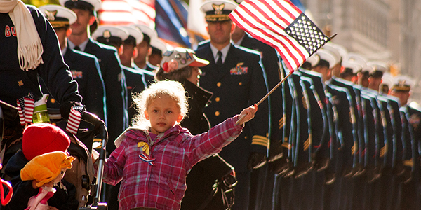 A young girl waves a US flag in a Veterans day parade in NYC
