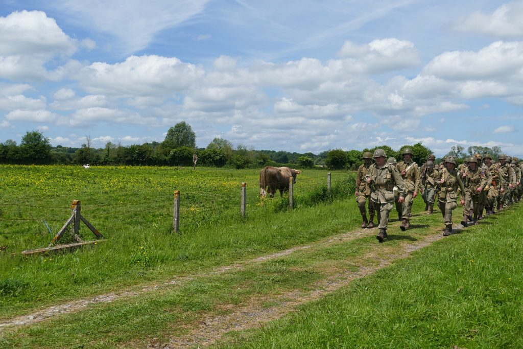 Reenactors marching along the same path as GIs 75 years ago