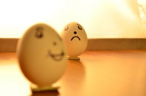 A sad expression drawn onto an egg that appears to be looking at another egg that appears happy