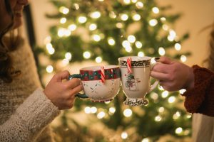 Two women holding Christmas mugs with candy canes hanging out of them
