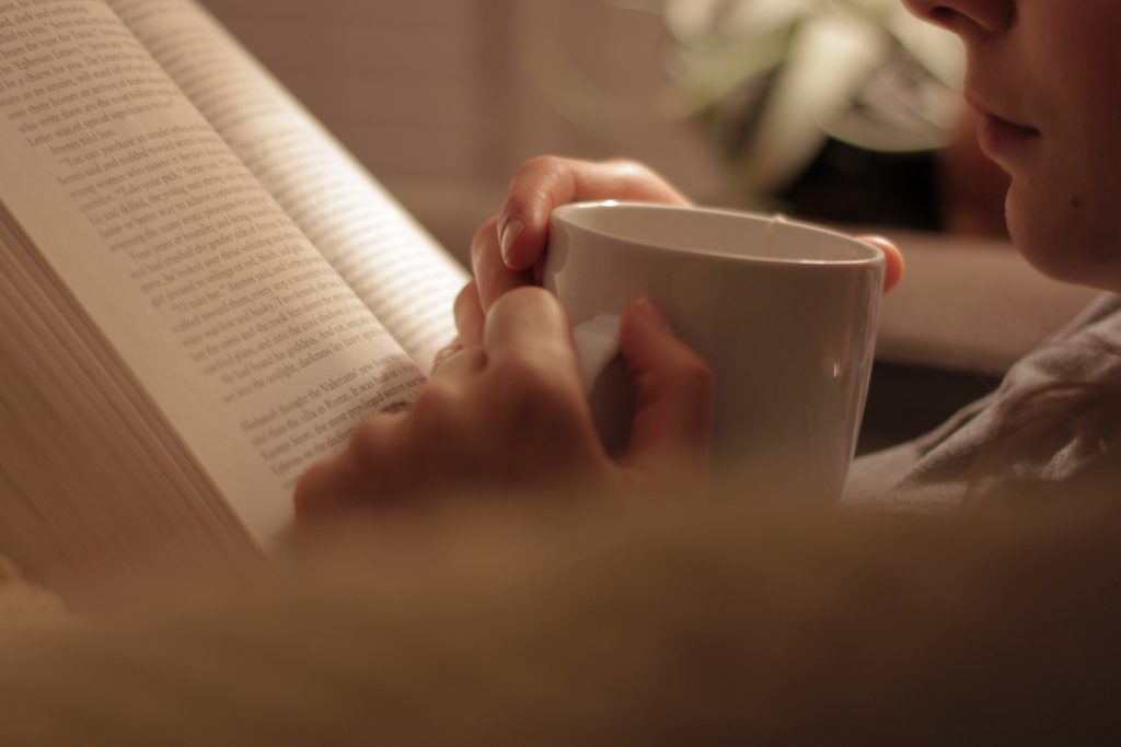 Woman reading a book sipping a warm beverage