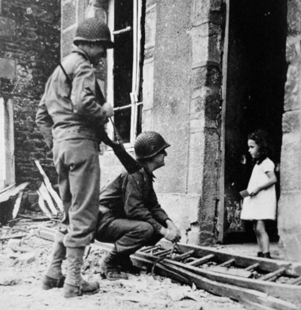 French girl in a doorway surrounded by rubble talking to two soldiers