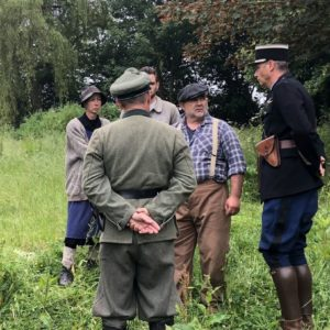 Four reinactors standing in a field while wearing WWII-era clothing