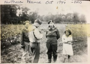 """Bob Miller and locals with the words """"Northern France Oct 1944 - Dad"""" written on it"""
