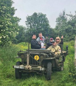 The Girl Who Wore Freedom crew in Normandy riding on a Jeep