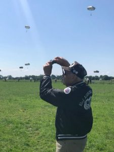 A veteran taking photos while parachutes fall from the sky