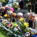 People laying flowers at a memorial in Normandy