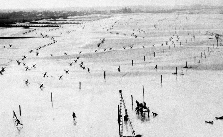 A black and white photo of a beach in Normandy with soldiers running across it